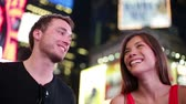 caminhada : Happy young couple on Times Square, Manhattan, New York City at night. Beautiful young multi-ethnic couple dating smiling having fun on date or as tourists in USA. Asian woman, Caucasian man. Stock Footage