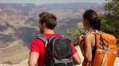 landscape : Hiking couple in Grand Canyon. Hikers walking and enjoying view of beautiful nature landscape of Grand Canyon, South Rim, Arizona, USA. Multiracial people, Asian woman, Caucasian man outdoor.