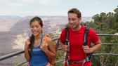caminhada : Hikers hiking in Grand Canyon. Active couple walking enjoying outdoor activity hike having fun as part of healthy lifestyle. Young multiracial couple, Caucasian man, Asian woman in Grand Canyon, USA.