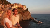 sorridente : Romantic couple in love by sunset on holidays travel. Young beautiful couple enjoying ocean view romance. Young people, man and woman traveling on vacation in Manarola, Cinque Terre, Liguria, Italy