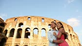 italy : Romantic couple on travel in Rome by Coliseum. Happy young traveler tourists in love embracing in front of Colosseum, Italy. Multicultural couple, Asian woman, Caucasian man. Stock Footage