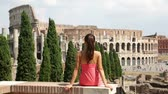 italiano : Rome tourist looking at Colosseum. Woman sitting in Roman Forum enjoying view of the famous Italian landmark, Coliseum. Tourism in Rome, Italy.