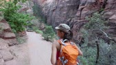 parque : Hiking woman on hike in Zion National Park. Happy woman hiker trekking on walking path in Zion Canyon wearing backpack. Healthy lifestyle image with multiracial Asian Caucasian girl in Utah, USA.