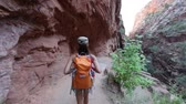 dráha : Hiking woman on hike in Zion National Park. Happy woman hiker trekking on walking path in Zion Canyon wearing backpack. Healthy lifestyle image with multiracial Asian Caucasian girl in Utah, USA.