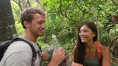 caminhada : Hikers walking in rain forest drinking water taking break. Hiking couple trekking through dense rainforest nature on Maui, Hawaii, USA. Healthy young sporty multiracial couple living active lifestyle. Stock Footage
