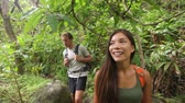 chuva : Hiking - hikers couple walking in rain forest jungle. Trekking couple on trek through dense rainforest nature on Maui, Hawaii, USA. Healthy young sporty multiracial couple living active lifestyle.