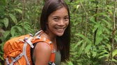 концепция : Hiking woman gesturing come along follow me, waving and hand looking at camera. Young female hiker walking with backpack in rain forest nature on Maui, Hawaii, USA. Mixed race Asian Caucasian girl. Стоковые видеозаписи
