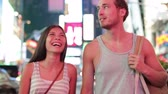 caminhada : Dating young couple happy in love talking and walking on Times Square, New York City at night. Beautiful young multiracial tourists having fun date on Manhattan, USA. Asian woman, Caucasian man.