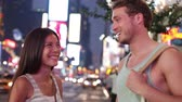 Dating young couple happy in love talking on Times Square, New York City at night. Beautiful young multiracial tourists having fun date on Manhattan, USA. Asian woman, Caucasian man.