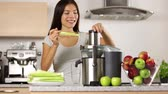perda de peso : Vegetable juice raw food - healthy eating woman with juicer juicing celery, green vegetables and apple fruits as part of wellness food. Beautiful happy mixed Asian woman with juice maker in kitchen. Vídeos