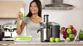 sorridente : Vegetable juice raw food - healthy eating woman with juicer juicing celery, green vegetables and apple fruits and drinking glass of green juice. happy mixed Asian woman with juice maker in kitchen. Stock Footage