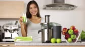 frondoso : Woman making green vegetable juice and drinking it fresh at home in kitchen giving thumbs up. Juicing and healthy eating happy woman making green vegetable and fruit juice.