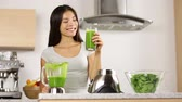 drinking : Woman making, pouring, drinking green vegetable smoothie with blender. Healthy eating lifestyle with young woman preparing blending smooithies drink with spinach, carrots, celery at home in kitchen. Stock Footage