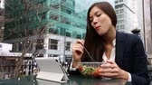 nova iorque : Businesswoman using tablet computer pc eating salad on lunch break in City Park living healthy lifestyle. Happy smiling mixed Asian young business woman in Bryant Park, Manhattan, New York City, USA Vídeos