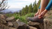 женщина : Hiker tying shoes on hike. Hiking shoe close up of woman tying laces female shoe outdoors in forest nature mountain. Footage from Gran Canaria, Canary Islands, Spain. Стоковые видеозаписи