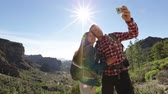 seyahat : Happy couple taking selfie photo image with smartphone hiking. Smiling couple taking self-portrait picture on hike in mountains. Young woman and man hikers on Gran Canaria, Canary Islands, Spain.