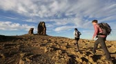 caminhada : Hikers hiking in beautiful landscape. Hiking couple man and woman trekking walking with backpacks in trail at sunset in mountains by Roque Nublo, Gran Canaria, Canary Islands, Spain. Stock Footage
