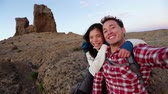 ázsiai : Happy couple taking selfie self-portrait photo hiking. Two friends or lovers on hike smiling at camera outdoors mountains by Roque Nublo, Gran Canaria, Canary Islands, Spain. Stock mozgókép