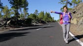 polegar : Travel woman hitchhiking. Beautiful young female hitchhiker by the road during vacation trip on, Tenerife, Canary Islands, Spain. Stock Footage