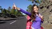 mixed race : Hitchhiker woman backpacker hitchhiking thumbing happy walking on road side during holiday travel. Beautiful outdoors woman model. Mixed race Asian Caucasian