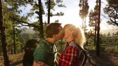 sunset : Couple kissing at sunset hiking in forest. Romantic hikers embracing in love enjoying view and romance at sunset in beautiful mountain landscape, on Gran Canaria, Canary Islands, Spain. Stock Footage