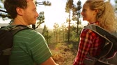 arka : Happy couple holding hands hiking in forest. Romantic hikers enjoying view and romance at sunset beautiful mountain landscape. Tilt from hands closeup to people talking. Gran Canaria, Canary Islands
