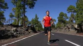 obuv : Sport running man - male runner training outdoors jogging on mountain road in forest landscape nature. Fit handsome jogger working out for marathon outside in summer. Real time. Dostupné videozáznamy