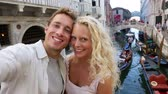 dva lidé : Venice couple taking selfie photo by Canal, Italy on travel together. Young happy couple on holidays or honeymoon having cute romantic vacation in Italy.
