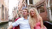 dva lidé : Romantic travel couple in Venice on Gondole ride romance in boat happy together on travel vacation holidays. Romantic young beautiful couple sailing in venetian canal in gondola. Italy, Europe.