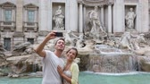 Řím : Tourist couple on travel taking selfie photo by Trevi Fountain in Rome, Italy. Happy young romantic couple traveling in Europe taking self-portrait with smartphone camera. Man and woman happy together