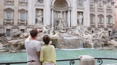 два человека : Rome couple taking picture photo with smartphone of Trevi Fountain, Italy. Happy young tourists couple traveling in Europe taking photos with smartphone camera. Man and woman happy. Стоковые видеозаписи