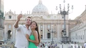 italiano : Tourists couple by Vatican city and St. Peters Basilica church in Rome. Happy travel woman and man taking selfie photo picture on romantic honeymoon in Italy.