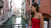 quente : Venice, Italy - woman in dress walking by canal over bridge smiling in Venice. Tourist girl in her 20s. Mixed race Asian Caucasian female model outside. Stock Footage