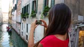 seyahat : Woman tourist taking picture photo in Venice, Italy. Travel girl using smartphone taking pictures of canal and gondola during vacation holidays in Europe.