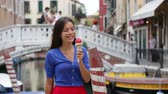 tatil : Ice cream eating woman in Venice, Italy on vacation travel enjoying gelato ice cream cone smiling happy walking. Tourist having fun eating italian food on holidays in Venice, Italy, Europe. Stok Video