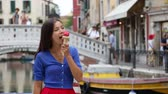 italiano : Ice cream eating woman in Venice, Italy on vacation travel enjoying gelato ice cream cone smiling happy walking. Tourist having fun eating italian food on holidays in Venice, Italy, Europe. Vídeos