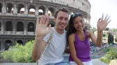 holky : Travel couple waving hello hands by Colosseum, Rome, Italy. Smiling young romantic couple traveling in Europe looking at camera smiling in front of Coliseum. Caucasian man and Asian woman.
