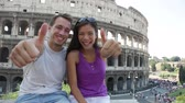 holky : Travel couple happy thumbs up by Colosseum, Rome, Italy. Smiling young romantic couple traveling in Europe looking at camera smiling in front of Coliseum. Caucasian man and Asian woman.