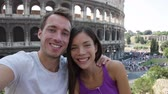 fotografia : Selfie - Romantic travel couple by Coliseum, Rome, Italy. Happy lovers on honeymoon sightseeing having fun in front of Colosseum. Woman and man in tourism travel concept.