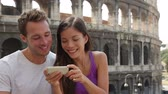 povo : Couple in Rome by Colosseum using smart phone looking at pictures or using travel app in Italy. Happy lovers on honeymoon sightseeing Coliseum. Love and travel concept with multiracial couple. Vídeos