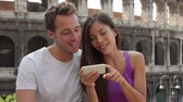 telemóvel : Rome couple by Colosseum using smartphone looking at pictures or using travel app in Italy. Happy lovers sightseeing Coliseum using smartphone. Love and travel concept with multiracial couple.