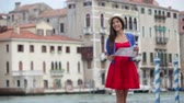 gezi : Travel woman tourist traveling in Venice, Italy holding map. Asian girl on vacation smiling happy by Grand Canal. Mixed race Asian Caucasian girl having fun during holidays in Europe. Stok Video