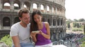 aplicativo : Couple using smart phone in Rome by Colosseum looking at pictures or using travel app in Italy. Happy lovers on honeymoon sightseeing Coliseum. Love and travel concept with multiracial couple.