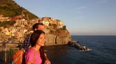 italy : Hiking couple portrait walking at sunset on holidays travel. Young backpacking Asian woman and Caucasian man enjoying ocean view on vacation in Manarola, Cinque Terre, Liguria, Italy