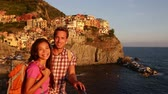 romantický : Hiking couple portrait looking at camera at sunset on holidays travel. Young backpacking Asian woman and Caucasian man enjoying ocean view on vacation in Manarola, Cinque Terre, Liguria, Italy