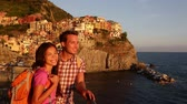 два человека : Romantic couple looking at sunset on holidays travel. Young backpacking Asian woman and Caucasian man enjoying ocean view. Young people on vacation in Manarola, Cinque Terre, Liguria, Italy Стоковые видеозаписи
