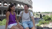 сидящий : Couple in Rome by Colosseum talking in Italy. Happy lovers on honeymoon sightseeing having fun in front of Coliseum. Love and travel concept with multiracial couple.