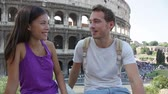 Řím : Couple in Rome by Colosseum talking in Italy. Happy young friends traveling and sightseeing having fun in front of Coliseum. Love and travel concept with multiracial couple.