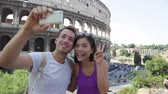 apaixonado : Happy travel couple taking selfie by Coliseum, Rome, Italy. Smiling young romantic couple traveling in Europe taking self portrait photo with smartphone camera in front of Colosseum. Man and woman.