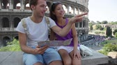 Řím : Tourists holding map by Colosseum sightseeing on travel vacation in Rome, Italy. Happy tourist couple, man and woman traveling on holidays in Europe smiling happy. Interracial Asian Caucasian couple